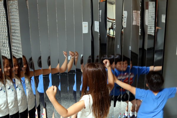 The kids in front of an array of mirrors at the Long Island Children's Museum.