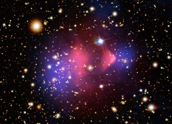 The Bullet Cluster, the first colliding galaxy clusters showing the separation between normal matter (pink, from the X-rays) and dark matter (blue, from gravitational lensing). Image credit: X-ray: NASA/CXC/CfA/M. Markevitch et al.; Lensing Map: NASA/STScI; ESO WFI; Magellan/U. Arizona/D. Clowe et al. Optical: NASA/STScI; Magellan/U. Arizona/D. Clowe et al.